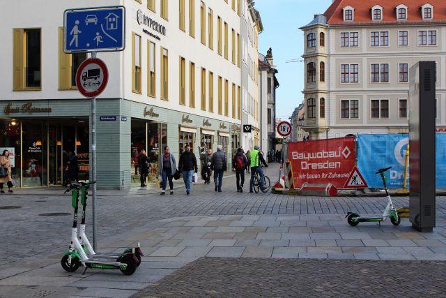 Zwei E-Scooter an einem Schild mit 'Spielstraße', ein weiterer Scooter schräg gegenüber. Pasanten.
