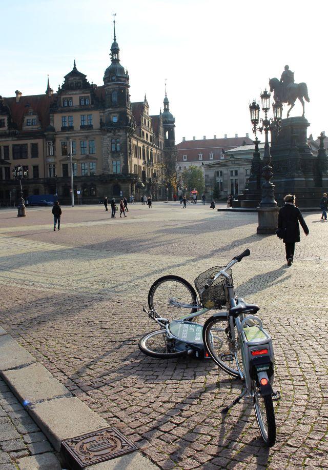 Ein Leihfahrrad steht, das andere liegt daneben auf dem Kopfsteinpflaster bei der Semperoper in Dresden.