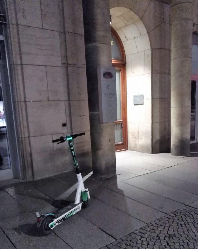 Grünweißer E-Scooter direkt neben einem Hauseingang vor einer steinernen Säule.