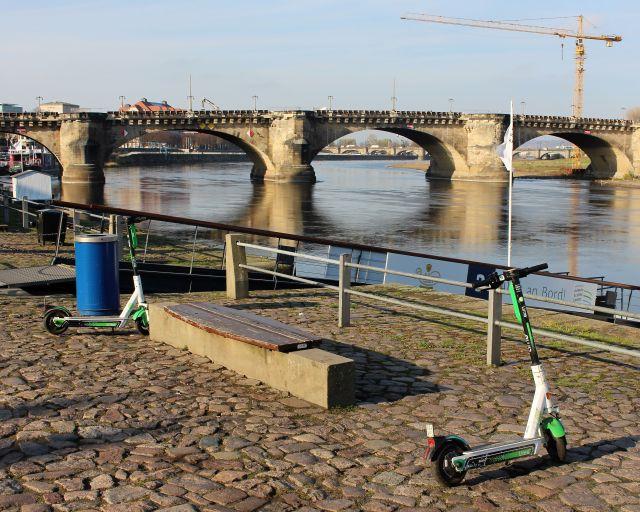 Zwei grün-weiße E-Scooter am Elbufer in Dresden. Sie stehen auf Kopfsteinpflaster. Im Hintergrund eine steinerne Brücke.