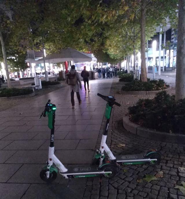 Zwei E-Scooter in einer Fußgängerzone. Sie stehen auf dem Weg.
