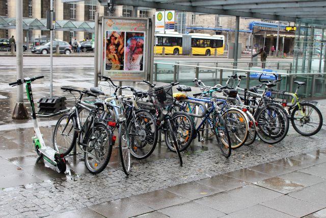 Mehrere Fahrräder in entsprechendem Ständer, danaben ein E-Scooter.