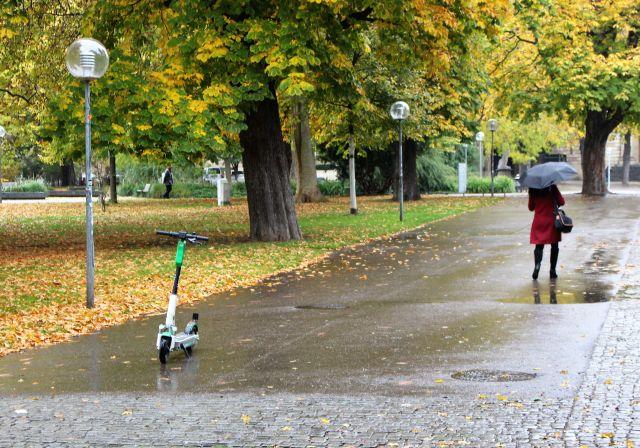 Ein weiß-grüner E-Scooter steht mitten auf einem asphaltierten Fuweg. Rechts hat ihn eine Fußgängerin passiert. Links und rechts Grasflächen und Bäume im Herbst.