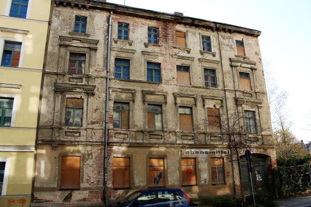 Vierstockiges Gebäude in desolatem äußeren Zustand Fassade bröckelt, Fenster zetlweise zugenagelt.