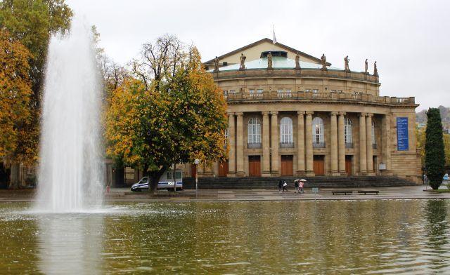 Das Opernhaus in Stuttgart, davor ein See mit einer Fontäne. Es regnet.