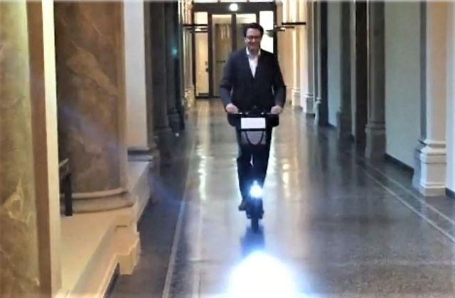 Verkehrsminister Scheuer fährt mit Elektrotretroller durch einen Büroflur.
