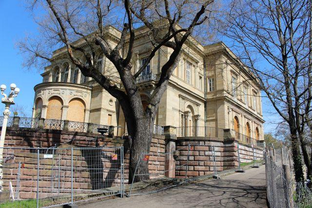 Ein Gebäude aus hellem Stein. Die Fensteröffnungen sind mit Holzplatten verschlossen. Im Vordergrund ein Baum.