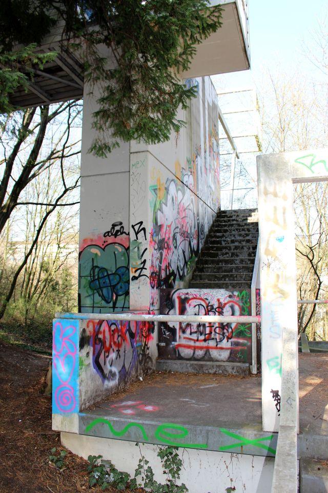 Graffiti auf Betonmauern, die zu einem Kunstprojekt gehören. Die Treppe ist gesperrt und nicht mehr begehbar. Alles ist in einem trostlosen Zustand.