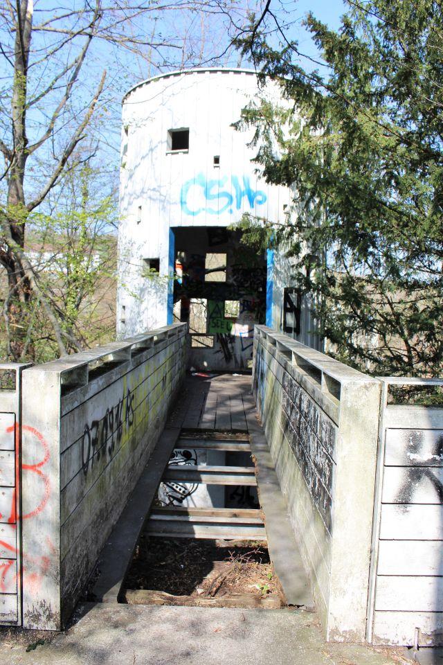 Verrotteter Steg zu einen Art Beton-Treppenhaus. Es fehlen Bretter, überall Graffiti.