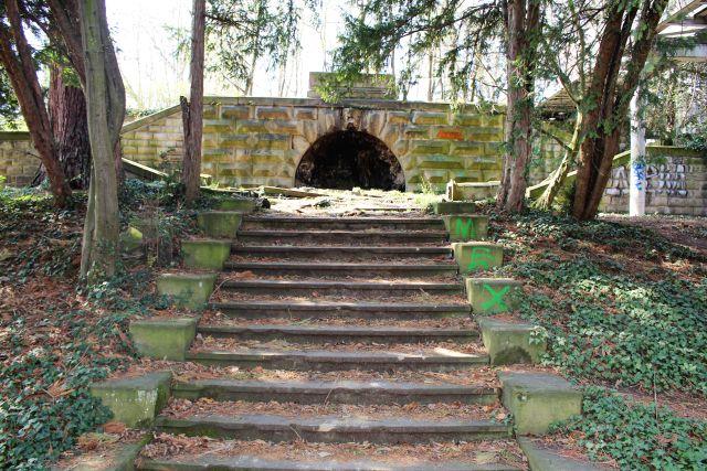 Vernachlässigte Treppe aus Naturstein führt zu den Resten der Villa Moser. Links und rechts Bäume.
