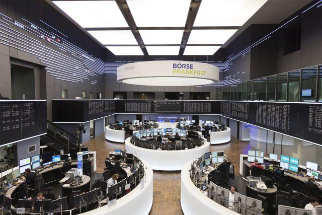 Blick in den Handelssaal der Börse in Frankfurt. Tische mit Bildschirmen sind in verschiedenen Kreisen angeordnet.