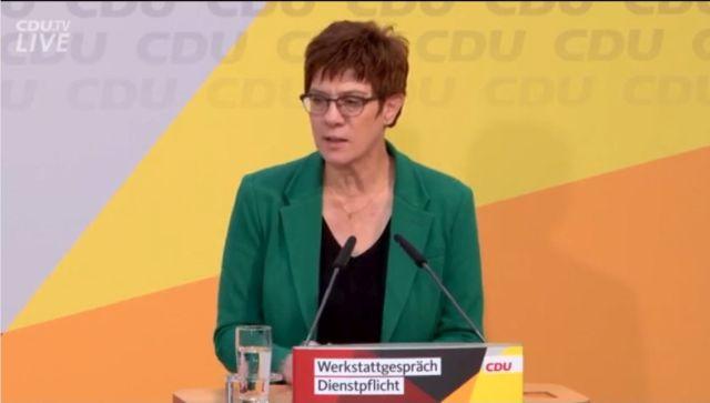 """Annegret Kramp-Karrenbauer mit braunen kurzen Haaren im grünen Blazer am Mikrofon. Aufschrift am Rednerpult """"Werkstattgespräch Dienstpflicht""""."""