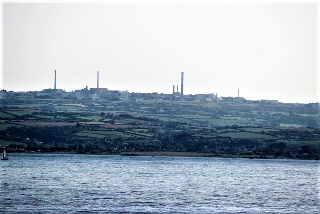 Die Kamine und Gebäude der Wiederaufbereitungsanlage in La Hague vom Meer aus gesehen.