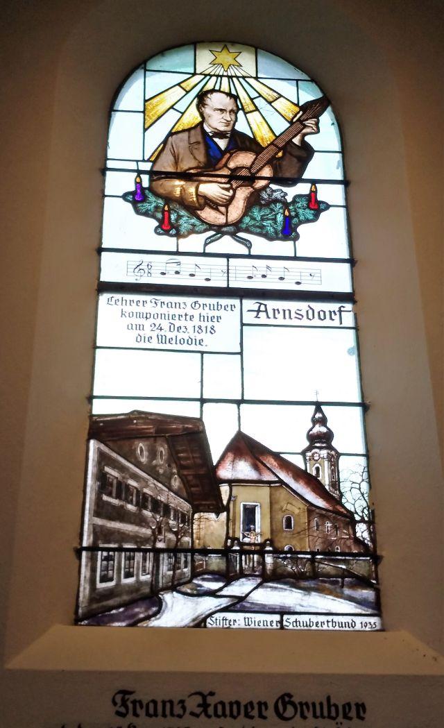 Franz Xaver Gruber in einem bunten Kirchenfenster. Mit Gitarre.