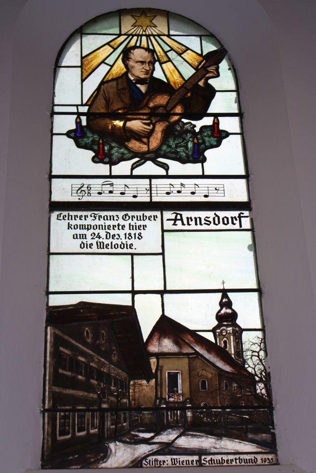 Franz Xaver Gruber mit Gitarre abgebildet in einem Fenster der Stille-Nacht-Kapelle.