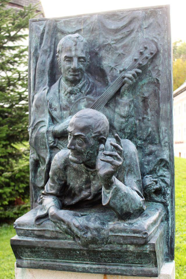 Dunkelgraue Metallskulptur mit herausgearbeiteten Oberkörpern von Joseph Mohr und Franz Xaver Gruber