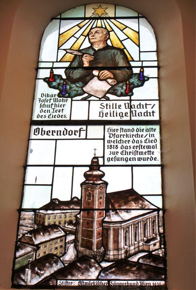 Kirchenfenster mit Joseph Moor, darunter eine Kirche.
