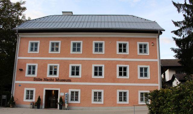 Das Stille-Nacht-Museum, der frühere Pfarrhof. Dreistockiges Gebäude mit rötlicher Fassade.