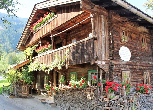 Tiroler Bauernhaus aus Holz mit Blumenschmuck.