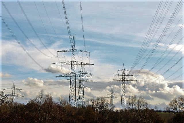 Stromleitungen an hohen Masten vor blauem Himmel bzw. weißen Wolken.