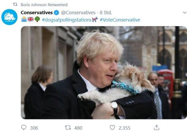 Boris Johnson mit einem kleinen Hund auf dem Arm.