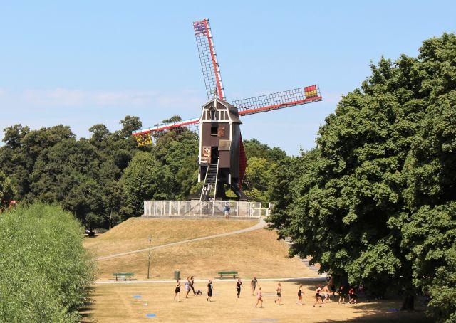 Eine Windmühle aus Holz auf einem kleinen Hügel. Im Vordergrund Menschen in einem Park.