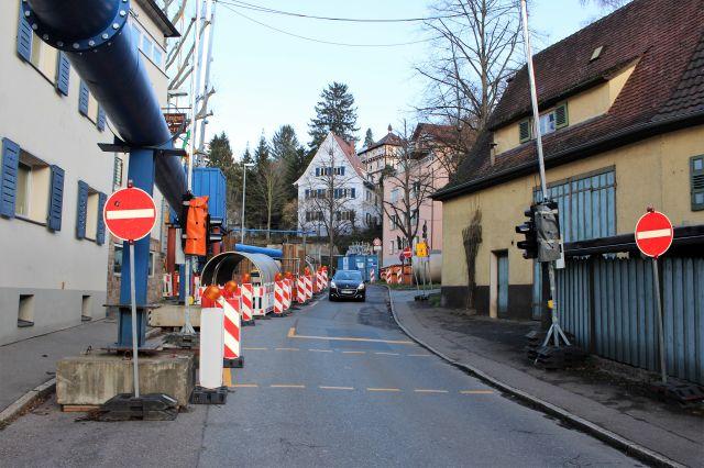 Durchfahrt verboten - zwei Schilder, verengte Straße. Ein Auto fährt stadteinwärts.