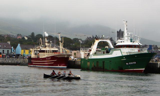Zwei Fischtrawler in grüner bzw. roter Farbe. Davor ein Ruderboot mit vier Personen.
