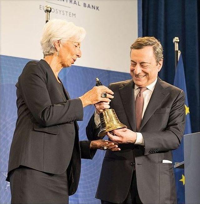 Links Christine Lagarde im dunklen Oberteil mit weißen Haaren, rechts Mario Draghi im dunklen Anzug mit rot-gemusterter Krawatte. Sie halten gemeinsam eine goldene Glocke.