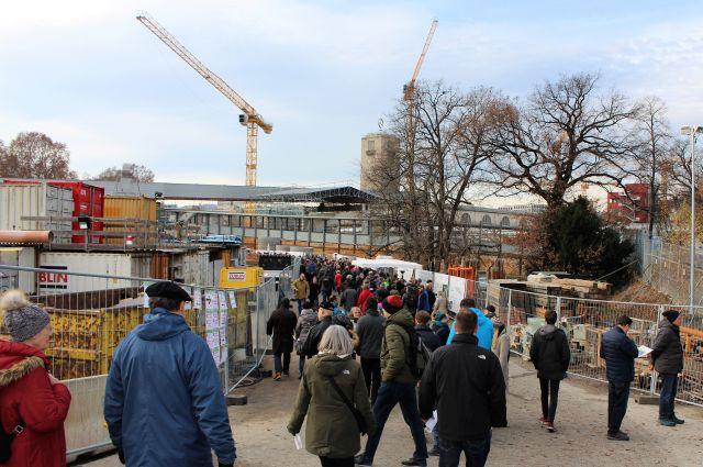 Zahlreiche Menschen bei den Tagen der offenen Baustelle. Im Hintergrund Kranen und der Turm des Bahnhofs.