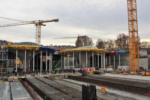 Zwei sogenannte Kelchstützen für den neuen Bahnhof in Stuttgart. Sie sind aus Beton und derzeit nach oben mit gelben Planen abgedeckt. Weiße Metallstützen sind noch an den Rändern der Kelchstützen zu sehen.