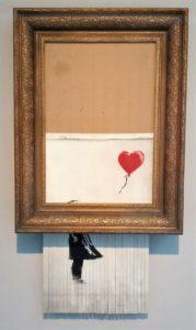 Banksy's 'Love is in the Bin'. Das Bild hängt zur Hälfte unten aus dem Rahmen, in Streifen geschreddert.