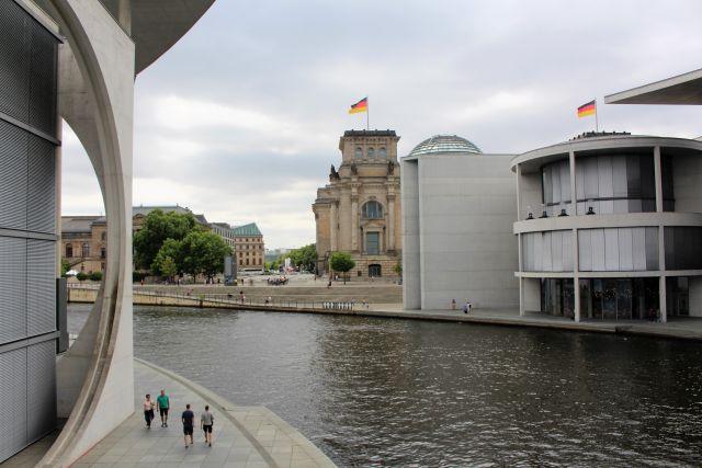 Blick auf den fast verdeckten Reichstag mit der Glaskuppel. Links und rechts Betonklötze mit Abgeordnetenbüros.
