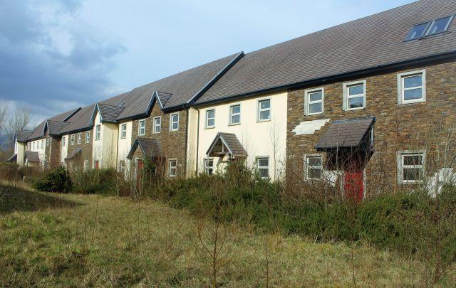 Nivcht ganz fertiggestellte Häuserzeile. Dunkle und hele Fassaden wechseln sich. Die Türen sind zugewachsen.