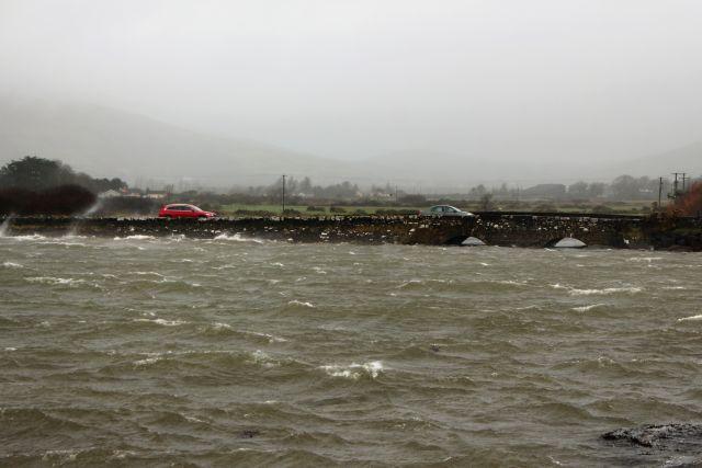 Steinerne Brücke mit zwei Bögen. Die Gisdcht der Wellen fliegt über die Straße, das Meerwasser reicht bis an die Brücke.