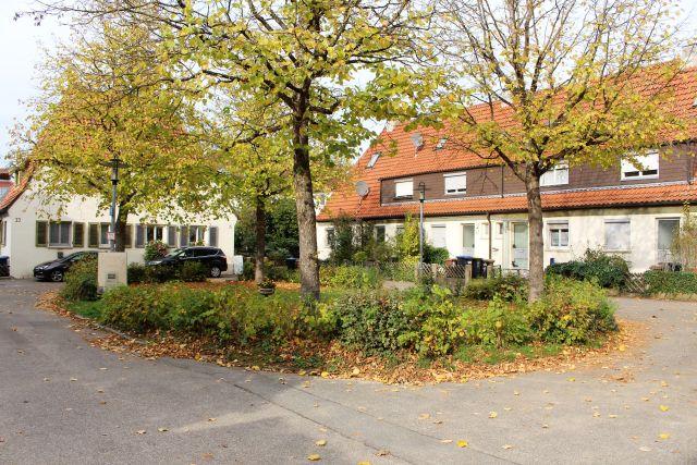 Innerstädtische Idylle. Ältere Häuser mit rotem Ziegeldach, davor Bäume und Gebüsch.