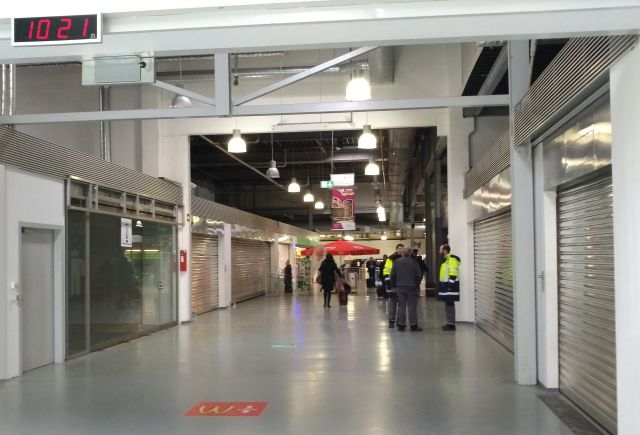 Leere Schaufenster und heruntergelasene Metallrollläden im Terminal 1. Einige Menschen, darunter Mitarbeiter des Flughafens.