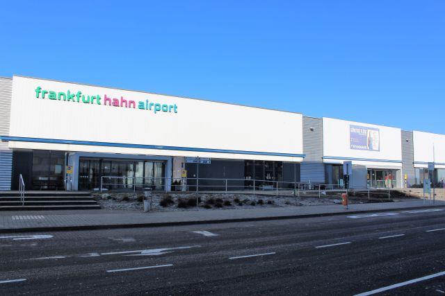 Weißes Gebäude mit der farbigen Aufschrift 'frankfurt hahn airport'. Keine Fahrzeuge oder Menschen zu sehen.