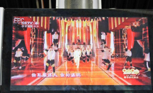 Bildschirm in der Wartehalle.Es zeigt einen Auschnitt aus einer chinesischen Fernsehsendung mit entsprechenden Schriftzeichen.