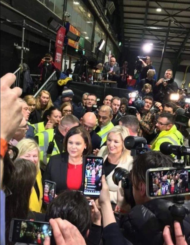 Mary Lou McDonald und Michelle O'Neill umgeben von Journalisten.