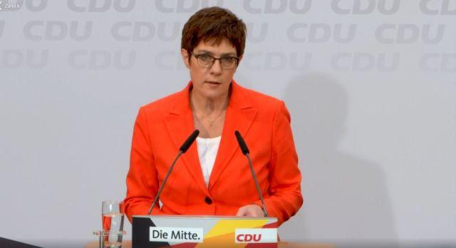 Kramp-Karrenbauer mit roter Jacke und weißem Shirt. Braune Haare und Brille. Vor einer Wand mit CDU-Schriftzügen.