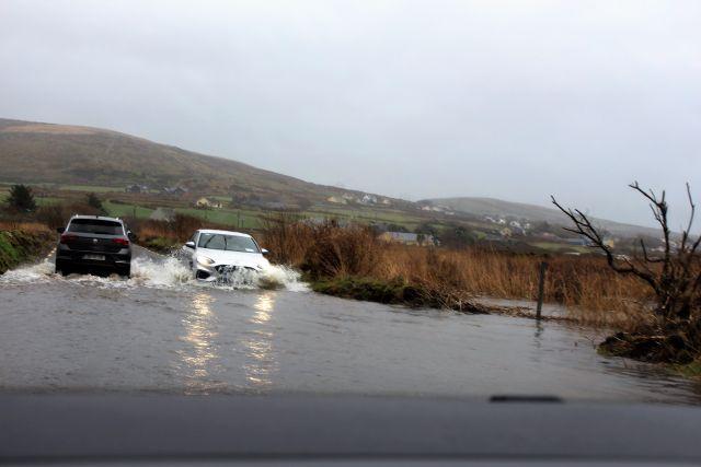Ein weißesrund ein dunkler Pkw begegnen sich und durchqueren eine überflutete Straße. Rechts im Bild Schilf und eine moorige Fläche.s
