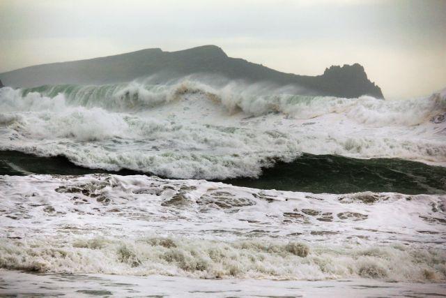 Wellenberge mit fliegender Gischt rollen auf den Strand zu, im Hintergrund eine Insel, die einem schlafenden Riesen gleicht.