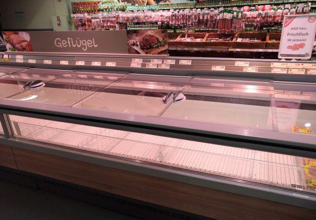 Leere Kühltruhe im Vordergrund, zahlreiche aufgehängte Salamiwürste im Hintergrund.