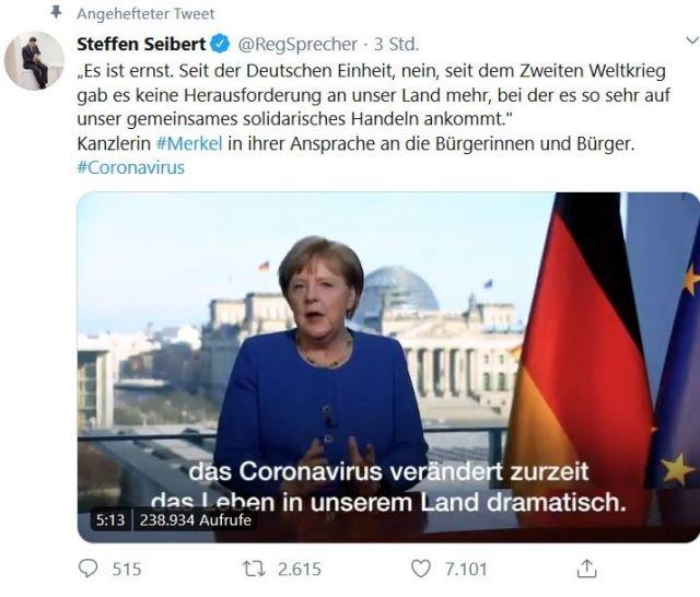 Bundeskanzlerin Merkel mit blauem Oberteil, rechts die deutsche und die EU-Flagge, im Hintergrund der Reichstag mit der gläsernen Kuppel.