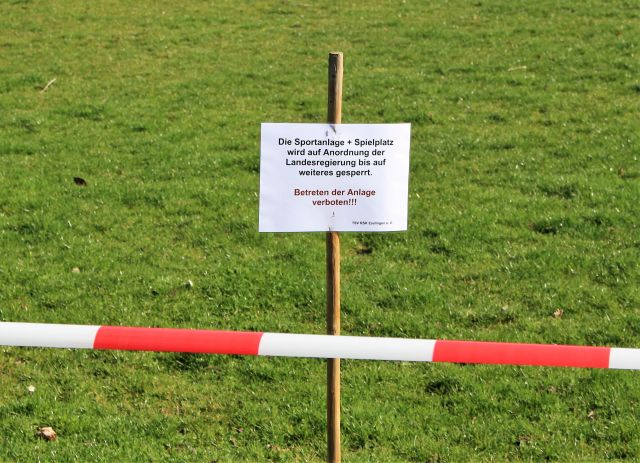 Gesperrter Sportplatz. Rot-weißes Absperrband und ein Schild mit dem Hinweis, dass die Sperrung auf Anordnung der Landesregierung erfolgt.