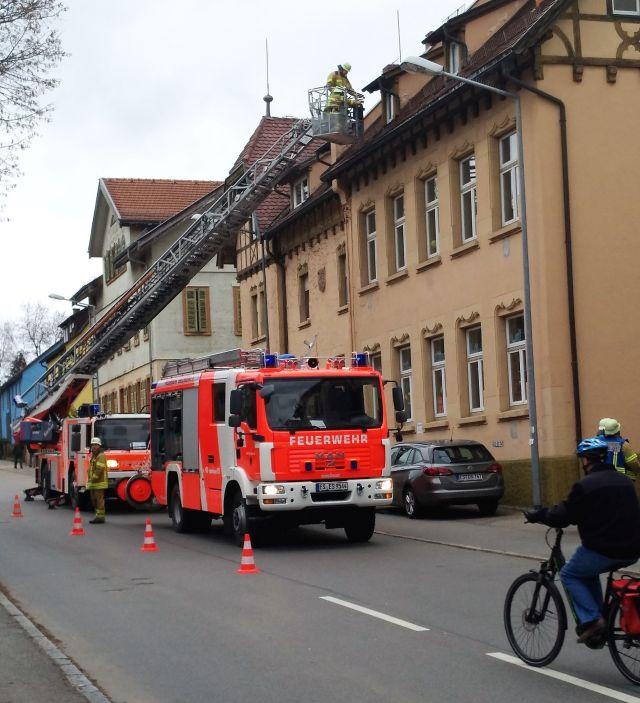 Feuerwehrfahrzeug mit ausgefahrener Drehleiter an einem mehrstöckigen Gebäude. Ein Feuerwehrmann ist am Dach zu erkennen.