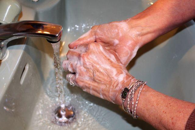 Zwei Hände mit Seife über Waschbecken (grüne Farbe).