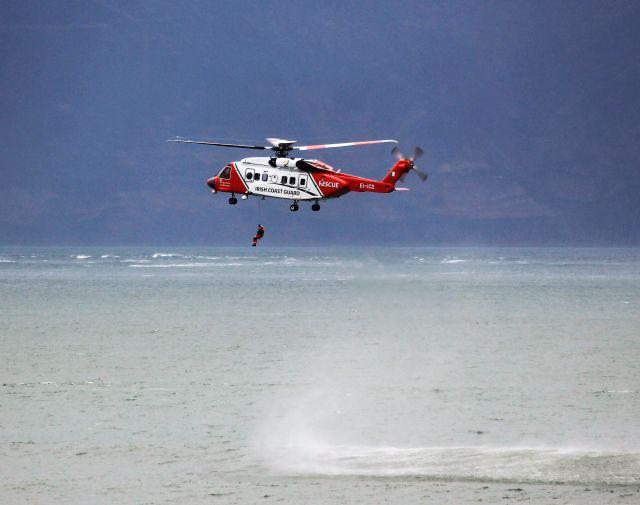 Weiß-roter Helikopter vor blauem Himmel üer dem Meer. Eine Person wird gerade an einem Tau nach unten gelassen.