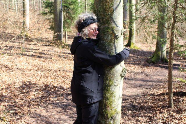 Frau mit dunkler Jacke und pasendem Ohrenband umarmt einen Baumstamm.